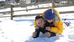 Το χαρούμενο κορίτσι στο κίτρινο παλτό τρίβει το πρόσωπο του φίλου της από το χιόνι Να αστειευτεί της νέας γυναίκας ερωτευμένης κ φιλμ μικρού μήκους