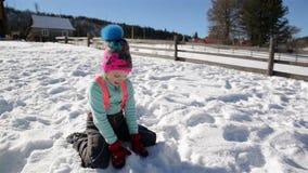 Το χαρούμενο μικρό κορίτσι έχει τη διασκέδαση στη συνεδρίαση χιονιού στο έδαφος και ρίχνει Snowflakes στον αέρα Ηλιόλουστη χειμερ απόθεμα βίντεο