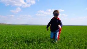 Το χαρούμενο παιδί σε ένα κοστούμι superhero, έναν κόκκινο επενδύτη και μια μάσκα τρέχει μέσω της πράσινης χλόης, εξετάζοντας τη  απόθεμα βίντεο