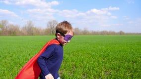 Το χαρούμενο παιδί σε ένα κοστούμι superhero, έναν κόκκινο επενδύτη και μια μάσκα τρέχει μέσω της πράσινης χλόης, που χαμογελά κα απόθεμα βίντεο