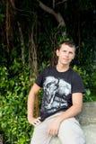 Το χαλαρωμένο ελκυστικό χαμογελώντας άτομο κάθεται στο βράχο Στοκ Φωτογραφίες