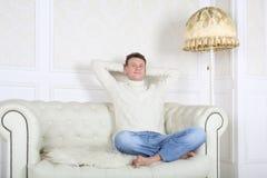 Το χαλαρωμένο ξυπόλυτο άτομο στο άσπρο πουλόβερ κάθεται στον καναπέ στοκ εικόνες
