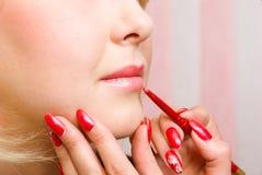 το χειλικό κραγιόν κοριτσιών χρωματίζει το κόκκινο visagiste Στοκ Εικόνες