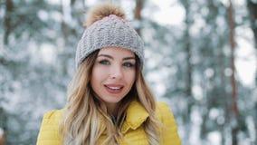 Το χειμερινό πορτρέτο μιας γοητευτικής νέας γυναίκας που εξετάζει το χαμογελώντας κορίτσι καμερών σε ένα κίτρινο κάτω σακάκι στέκ απόθεμα βίντεο