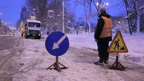 Το χιόνι-άροτρο αφαιρεί το χιόνι από την οδό πόλεων Ο εργαζόμενος εγκαθιστά τα οδικά σημάδια προειδοποίησης απόθεμα βίντεο