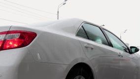 Το χιόνι αφορά αργά το αυτοκίνητο, κινηματογράφηση σε πρώτο πλάνο σκηνή Ένα άσπρο αυτοκίνητο στέκεται σε χιονοπτώσεις Λεπτομέρειε απόθεμα βίντεο