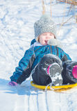 Το χιόνι γλιστρά το πηγαίνοντας παιδί και είναι ευτυχές στοκ φωτογραφία