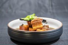 Το χοιρινό κρέας στη γλυκιά καφετιά σάλτσα, αυτό είναι στο γλυκό ζωμό στο μαύρο υπόβαθρο στοκ εικόνα