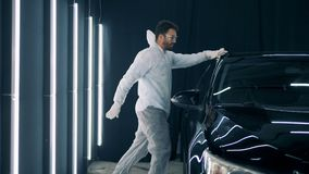 Το χορεύοντας μέλος των ενόπλων δυνάμεων καθαρίζει ένα αυτοκίνητο σε ένα γκαράζ φιλμ μικρού μήκους