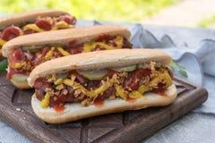 Το χοτ-ντογκ με το μπέϊκον τύλιξε το λουκάνικο, το κέτσαπ, την κίτρινη μουστάρδα, το τηγανισμένα κρεμμύδι και τα τουρσιά Στοκ Φωτογραφίες