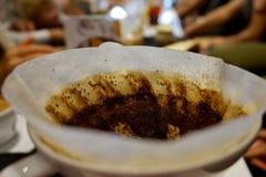 Το χρησιμοποιημένο κωνικό φίλτρο καφέ χύνει πέρα από τον κατασκευαστή καφέ στοκ φωτογραφίες