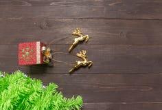 Το χριστουγεννιάτικο δέντρο και οι τάρανδοι είναι ανοικτά στο ξύλινο υπόβαθρο Στοκ Φωτογραφίες