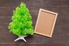 Το χριστουγεννιάτικο δέντρο και το πλαίσιο εικόνων είναι στο ξύλινο υπόβαθρο Στοκ Φωτογραφία