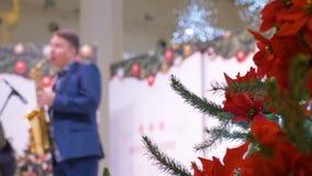 Το χριστουγεννιάτικο δέντρο, είναι διακοσμημένο σε ένα εμπορικό κέντρο Στο υπόβαθρο, ο μουσικός παίζει το saxophone εθνικό verdur φιλμ μικρού μήκους
