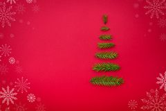Το χριστουγεννιάτικο δέντρο συμβόλων από ένα έλατο διακλαδίζεται στο κόκκινο υπόβαθρο σπόλα Στοκ Φωτογραφίες