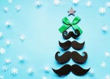 Το χριστουγεννιάτικο δέντρο των μουστακιών, με ένα πράσινο τόξο και ένα αστέρι, snowflakes διασκόρπισε σε ένα μπλε υπόβαθρο, κάρτ στοκ φωτογραφίες