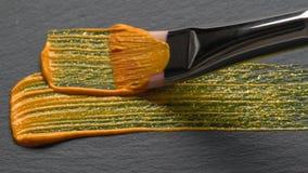 Το χρυσό ακρυλικό χρώμα με ακτινοβολεί απόθεμα βίντεο
