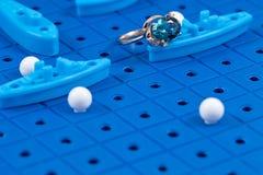 Το χρυσό δαχτυλίδι βρίσκεται στον πίνακα παιχνιδιών με τα στρατιωτικά σκάφη παιχνιδιών Στοκ εικόνα με δικαίωμα ελεύθερης χρήσης