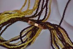 Το χρυσό δαχτυλίδι και οι χρωματισμένες χάντρες είναι σε ένα ελαφρύ ύφασμα στοκ εικόνες με δικαίωμα ελεύθερης χρήσης