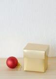 Το χρυσό κιβώτιο δώρων και η κόκκινη σφαίρα διακοσμούν στον πίνακα άνω του BA τοίχων μορίων Στοκ φωτογραφία με δικαίωμα ελεύθερης χρήσης