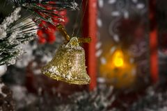 Το χρυσό κουδούνι Χριστουγέννων κρεμά σε έναν κλάδο πεύκων ενάντια σε ένα κόκκινο φανάρι με ένα κερί Στοκ φωτογραφία με δικαίωμα ελεύθερης χρήσης