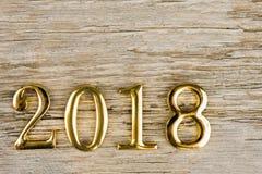 Το χρυσό μέταλλο λογαριάζει το 2018 σε ένα ξύλινο υπόβαθρο Στοκ Φωτογραφίες