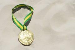 Το χρυσό μετάλλιο με τη Βραζιλία χρωματίζει την κορδέλλα στην άμμο Στοκ φωτογραφία με δικαίωμα ελεύθερης χρήσης