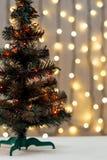 Το χρυσό υπόβαθρο Χριστουγέννων de-η γιρλάντα φω'των με το διακοσμημένο δέντρο Στοκ Φωτογραφίες