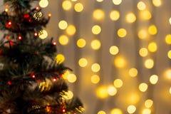 Το χρυσό υπόβαθρο Χριστουγέννων de-η γιρλάντα φω'των με το διακοσμημένο δέντρο Στοκ φωτογραφία με δικαίωμα ελεύθερης χρήσης