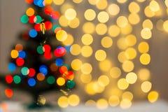 Το χρυσό υπόβαθρο Χριστουγέννων de-η γιρλάντα φω'των με το διακοσμημένο δέντρο Στοκ εικόνα με δικαίωμα ελεύθερης χρήσης