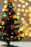 Το χρυσό υπόβαθρο Χριστουγέννων de-η γιρλάντα φω'των με το διακοσμημένο δέντρο Στοκ Φωτογραφία