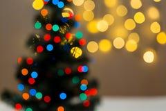 Το χρυσό υπόβαθρο Χριστουγέννων de-η γιρλάντα φω'των με το διακοσμημένο δέντρο Στοκ εικόνες με δικαίωμα ελεύθερης χρήσης