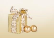 Το χρυσό δώρο τύλιξε τις σφαίρες παρόντος και Χριστουγέννων στοκ εικόνες με δικαίωμα ελεύθερης χρήσης