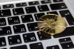 Το χρυσό bitcoin βρίσκεται στο πληκτρολόγιο του σημειωματάριου στοκ φωτογραφίες