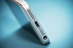 Το χρυσό iPhone της Apple 5s στο μπλε υπόβαθρο εγγράφου Στοκ φωτογραφία με δικαίωμα ελεύθερης χρήσης