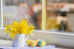Το χρωματισμένο αυγό Πάσχας και το λευκό λίγα μπορούν με τα κίτρινα λουλούδια πλησίον Στοκ Φωτογραφίες