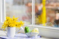 Το χρωματισμένο αυγό Πάσχας και το λευκό λίγα μπορούν με τα κίτρινα λουλούδια πλησίον Στοκ Εικόνες