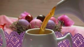 Το χρωματισμένο ρόδινο αυγό Πάσχας βρίσκεται Τσάι που χύνεται στο φλυτζάνι απόθεμα βίντεο