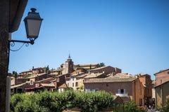 Το χρωματισμένο ochre χωριό κορυφών υψώματος Rousillon, Vaucluse, αποδεικνύεται Στοκ Φωτογραφία