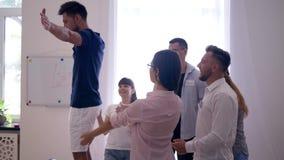 Το χτίσιμο ομάδας, νεαρός άνδρας στην καρέκλα αφορά κάτω την πλάτη εμπιστεμένος τους συναδέλφους του ότι τον πιάνουν απόθεμα βίντεο