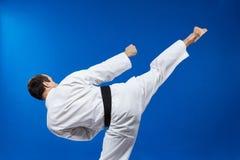 Το χτύπημα roundhouse κτυπά τον αθλητή στο karategi Στοκ Φωτογραφία