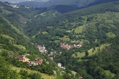 Το χωριό με το κόκκινο τα σπίτια στα δασώδη βουνά σε Κόσοβο Στοκ Εικόνες