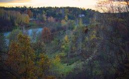 το χωριό στεγάζει κοντά στο λόφο με τα δέντρα και τον ποταμό φθινοπώρου Στοκ φωτογραφία με δικαίωμα ελεύθερης χρήσης