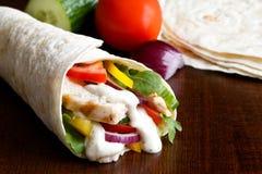 Το ψημένο στη σχάρα tortilla κοτόπουλου και σαλάτας περικάλυμμα με την άσπρη σάλτσα απομονώνει Στοκ Εικόνες