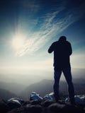 Το ψηλό άτομο παίρνει τη φωτογραφία από τη κάμερα καθρεφτών στο λαιμό Χιονώδης βράχος Στοκ Εικόνα
