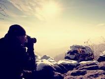 Το ψηλό άτομο παίρνει τη φωτογραφία από τη κάμερα καθρεφτών στο λαιμό Χιονώδης βράχος Στοκ Φωτογραφίες
