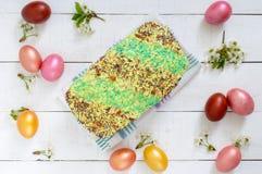 Το ψωμί Πάσχας kulich με το λούστρο, ζωηρόχρωμη ζάχαρη ψεκάζει Χρωματισμένα χρωματισμένα αυγά Στοκ Εικόνες