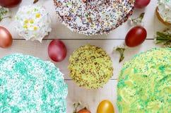 Το ψωμί Πάσχας kulich με το λούστρο, ζωηρόχρωμη ζάχαρη ψεκάζει Χρωματισμένα χρωματισμένα αυγά Στοκ Φωτογραφία