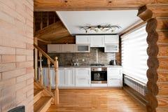 Το δωμάτιο κουζινών σε μια αγροτική καμπίνα κούτσουρων, στα βουνά με ένα όμορφο εσωτερικό σπίτι των κούτσουρων πεύκων Στοκ φωτογραφία με δικαίωμα ελεύθερης χρήσης