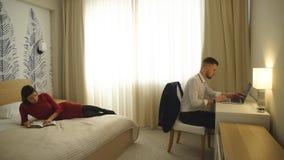 Το δωμάτιο ξενοδοχείου, το άτομο στον υπολογιστή, περιοδικό ανάγνωσης κοριτσιών στο κρεβάτι απόθεμα βίντεο